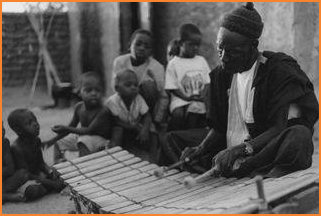 Grandfather Wamian Kone plays the bala xylophone for his grandchildren and friends.